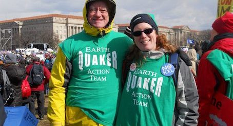 "George and Ingrid Lakey stand with their arms around each other at a rally at the U.S Capitol. They wear green t-shirts reading ""Earth Quaker Action Team."""