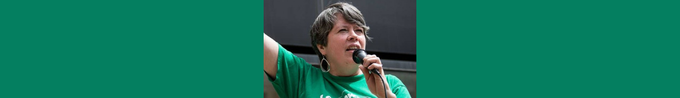 Image of Eileen Flanagan speaking into a microphone and raising a hand